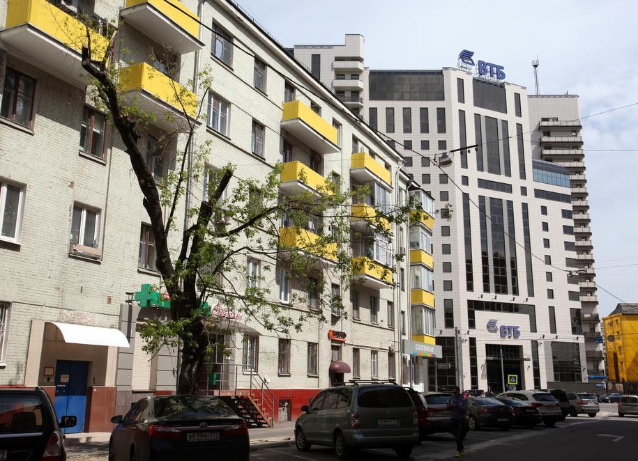 Пятиэтажка с желтыми балконами и здание ВТБ