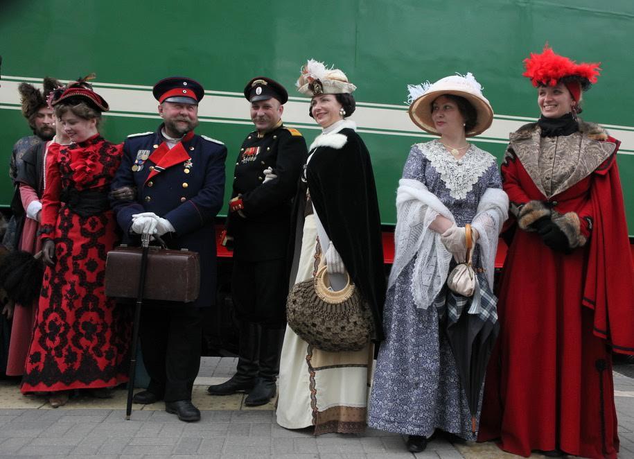 Участники-реконструкторы фестиваля Времена и эпохи на Рижском вокзале перед старинным поездом