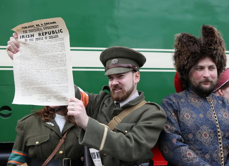 Участники-реконструкторы фестиваля Времена и эпохи на Рижском вокзале перед старинным поездом с газетой