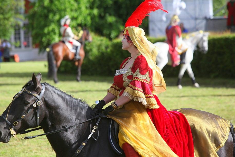 Всадница верхом на черной лошади