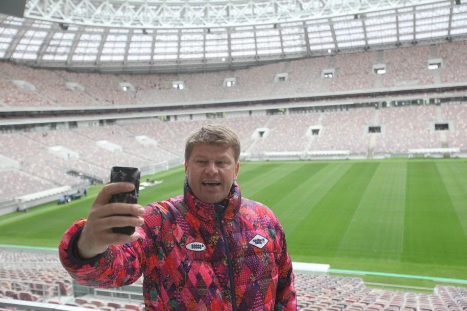 Дмитрий Губерниев во время селфи на фоне поля и трибун спортивной арены в Лужниках