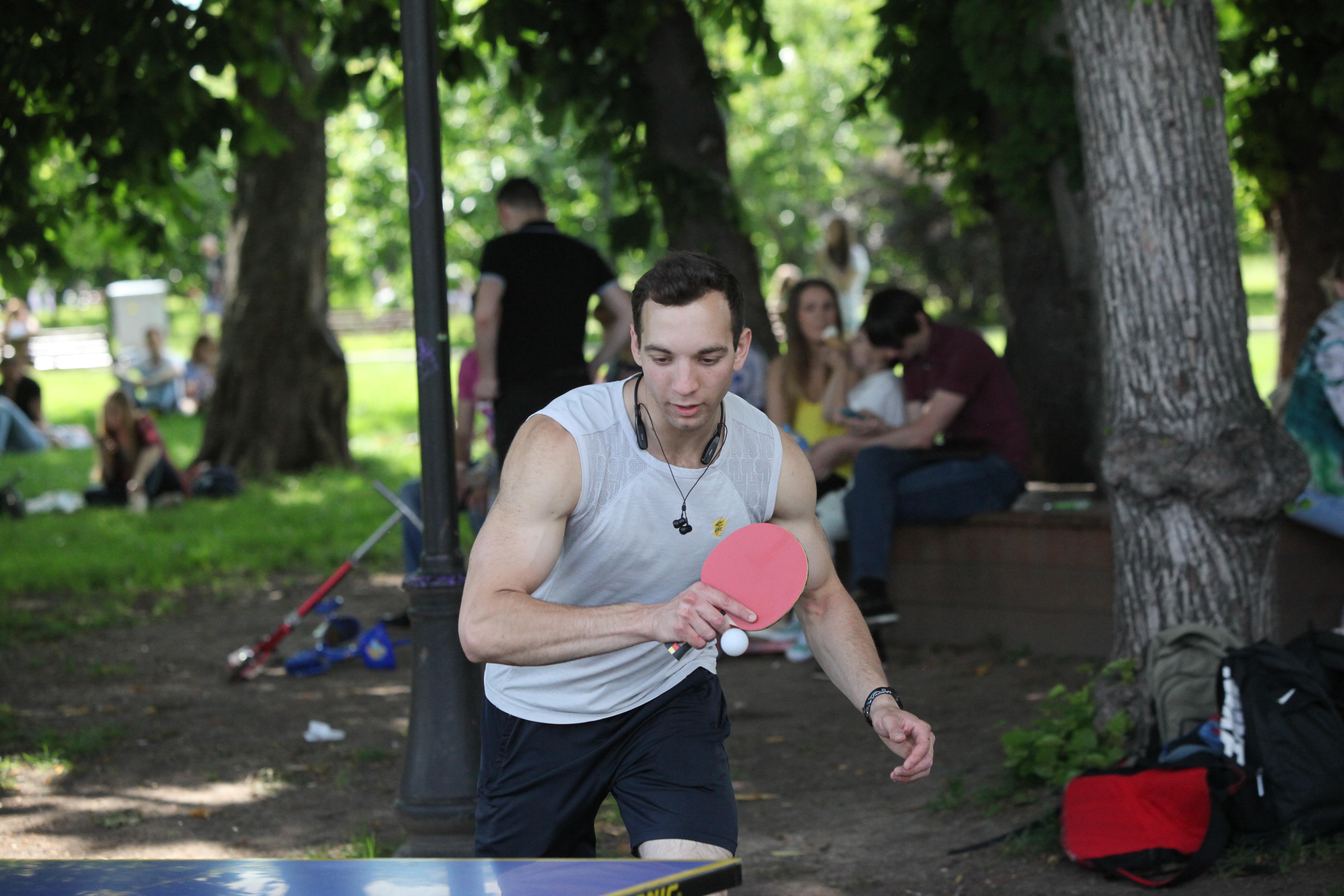 Посетитель парка во время игры в настольный теннис