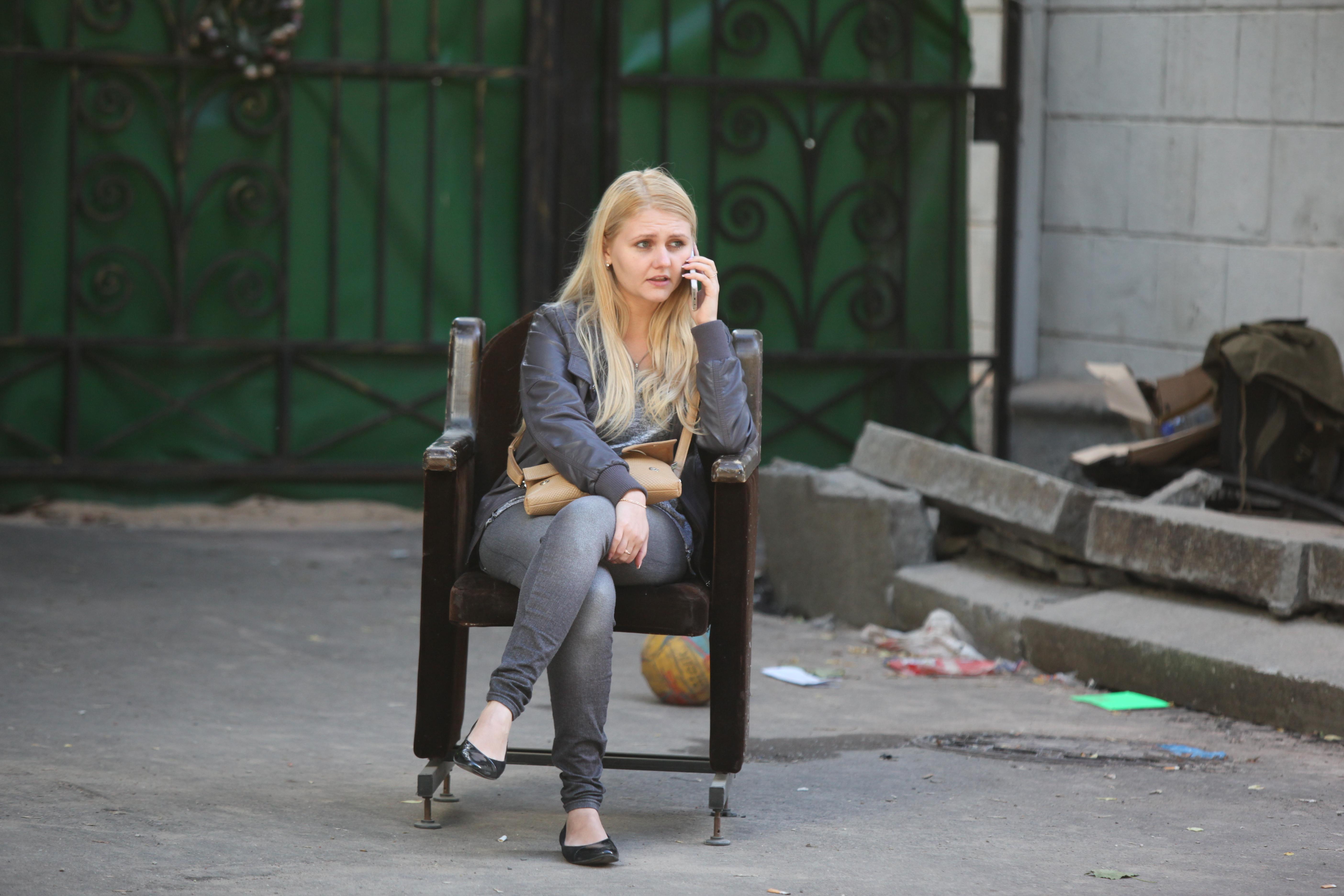 Женщина на улице в старом кресле