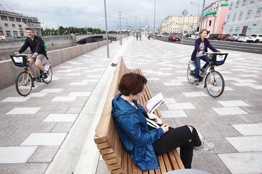 Велосипедисты и читательница на лавочке на набережной в Москве
