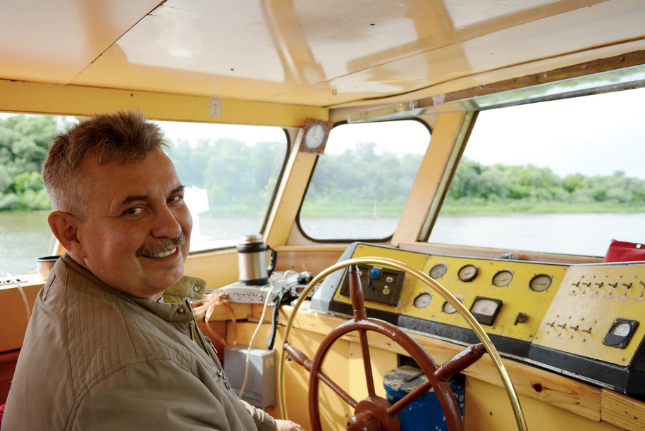 Капитан-механик катера Дружба Алексей Сорокин у штурвала