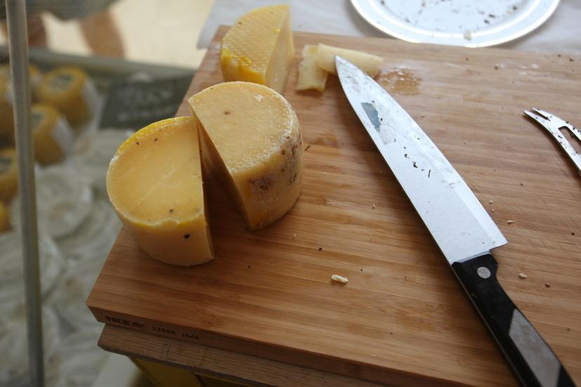 Нож и сыр на деревянной разделочной доске