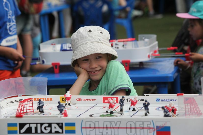 Мальчик у игры настольный хоккей на фестивале Moscow City Games в Лужниках