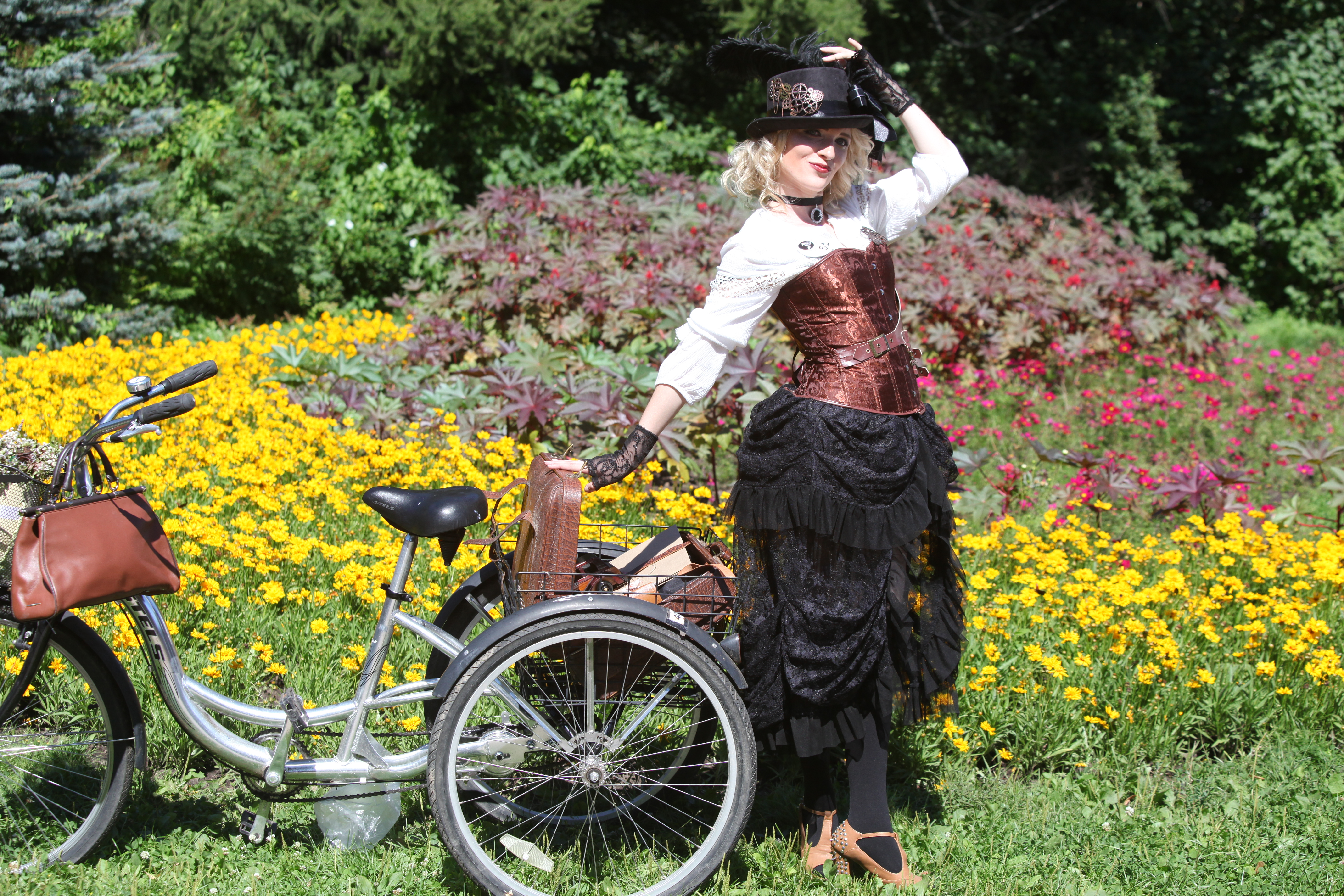 Участница велопарада в Сокольниках в старинном платье и рядом старинный трехколесный велосипед