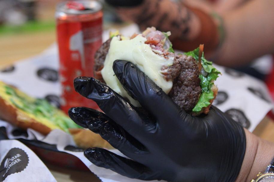 Бургер и черные перчатки вместо салфеток в бургерной BLACK STAR BURGER