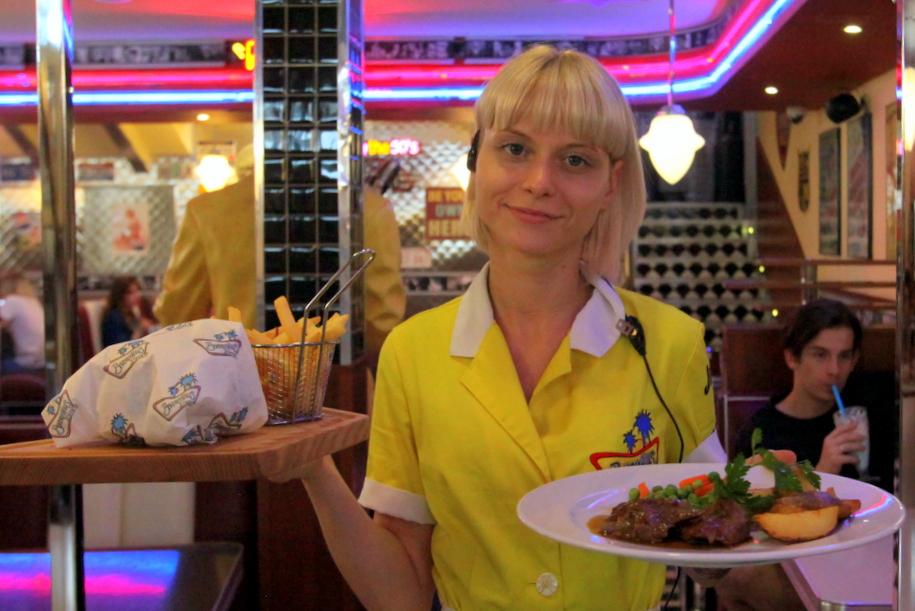 Официантка бургерной BEVERLY HILLS DINER с бургером картошкой и мясом на тарелке
