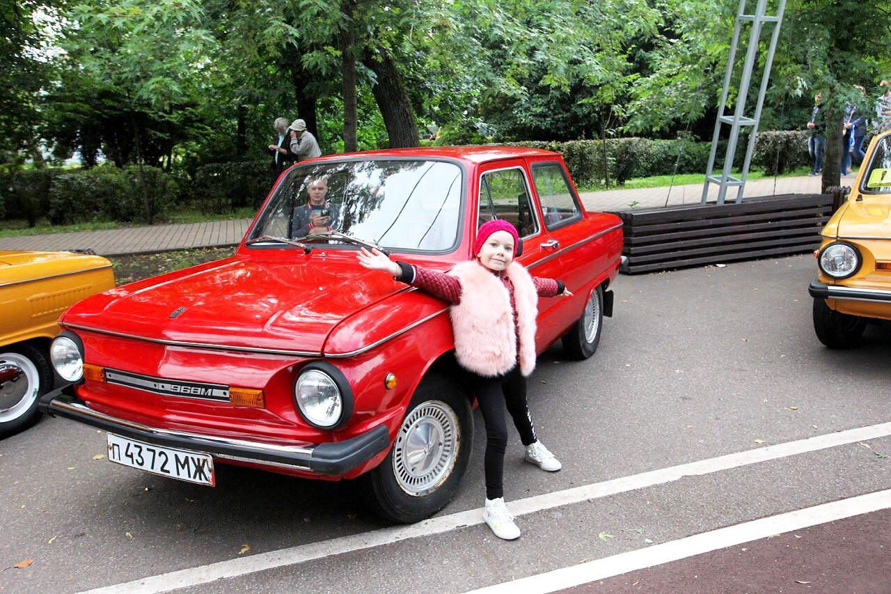 Девочка у красного ретро-автомобиля