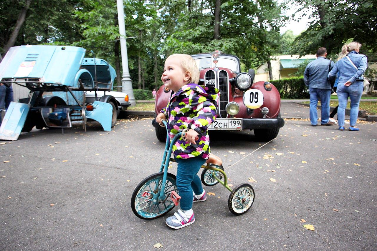 Ребенок на трехколесном велосипеде перед ретро-автомобилем