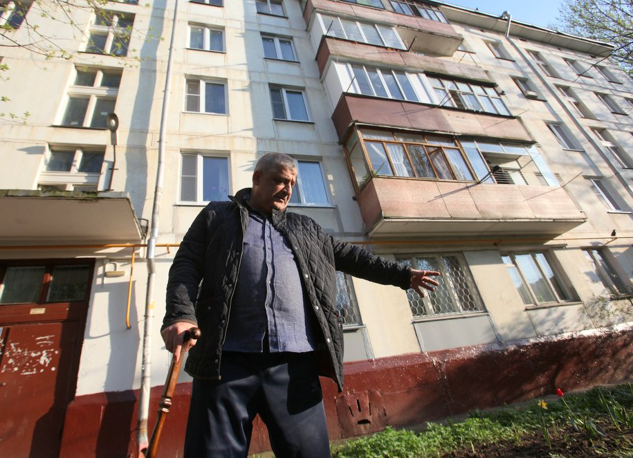 Пенсионер на фоне пятиэтажного дома
