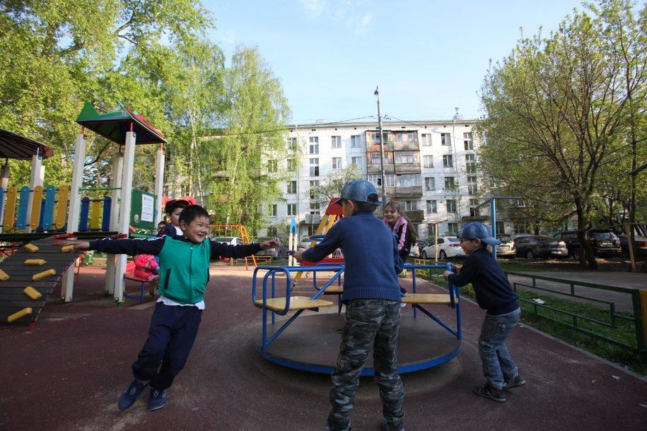 Дети на игровой площадке во дворе пятиэтажного дома