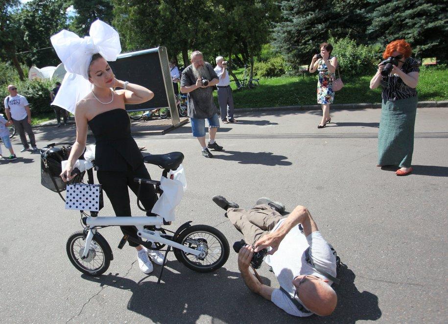 Фотографы и велосипедистка с белым бантом