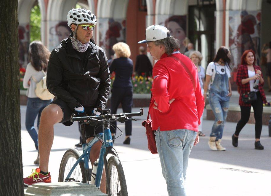 Велосипедист в шлеме и прохожий