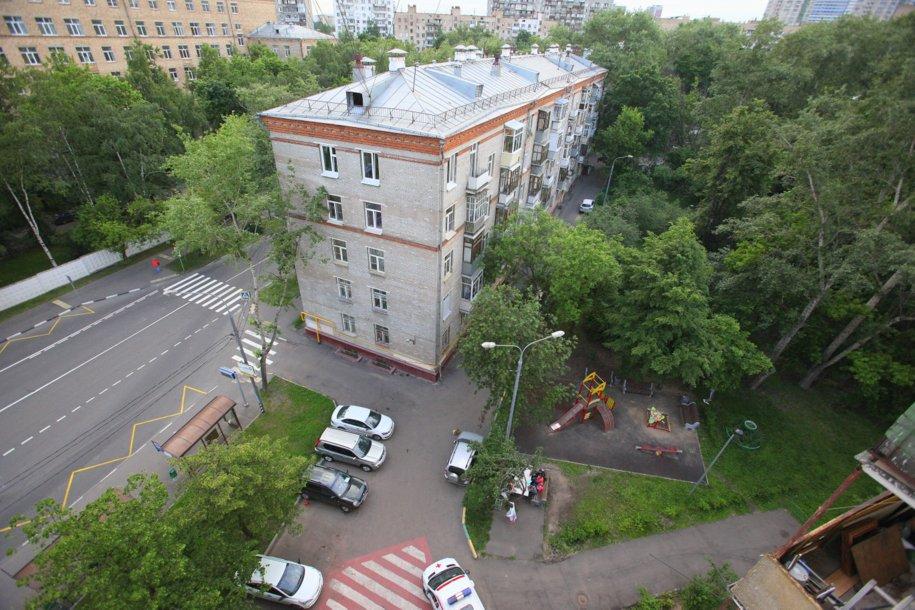 Вид сверху на пятиэтажный дом и детскую площадку
