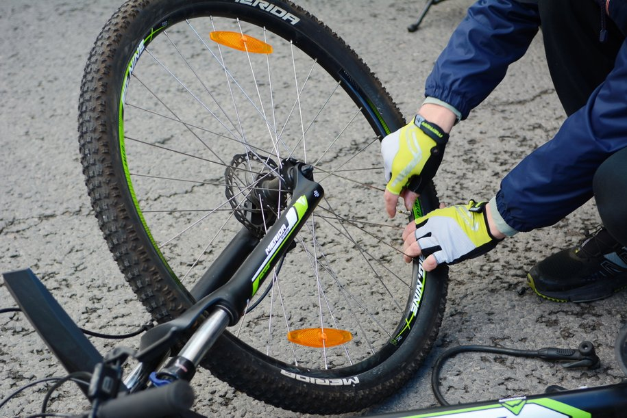 Велосипедное колесо и руки в перчатках